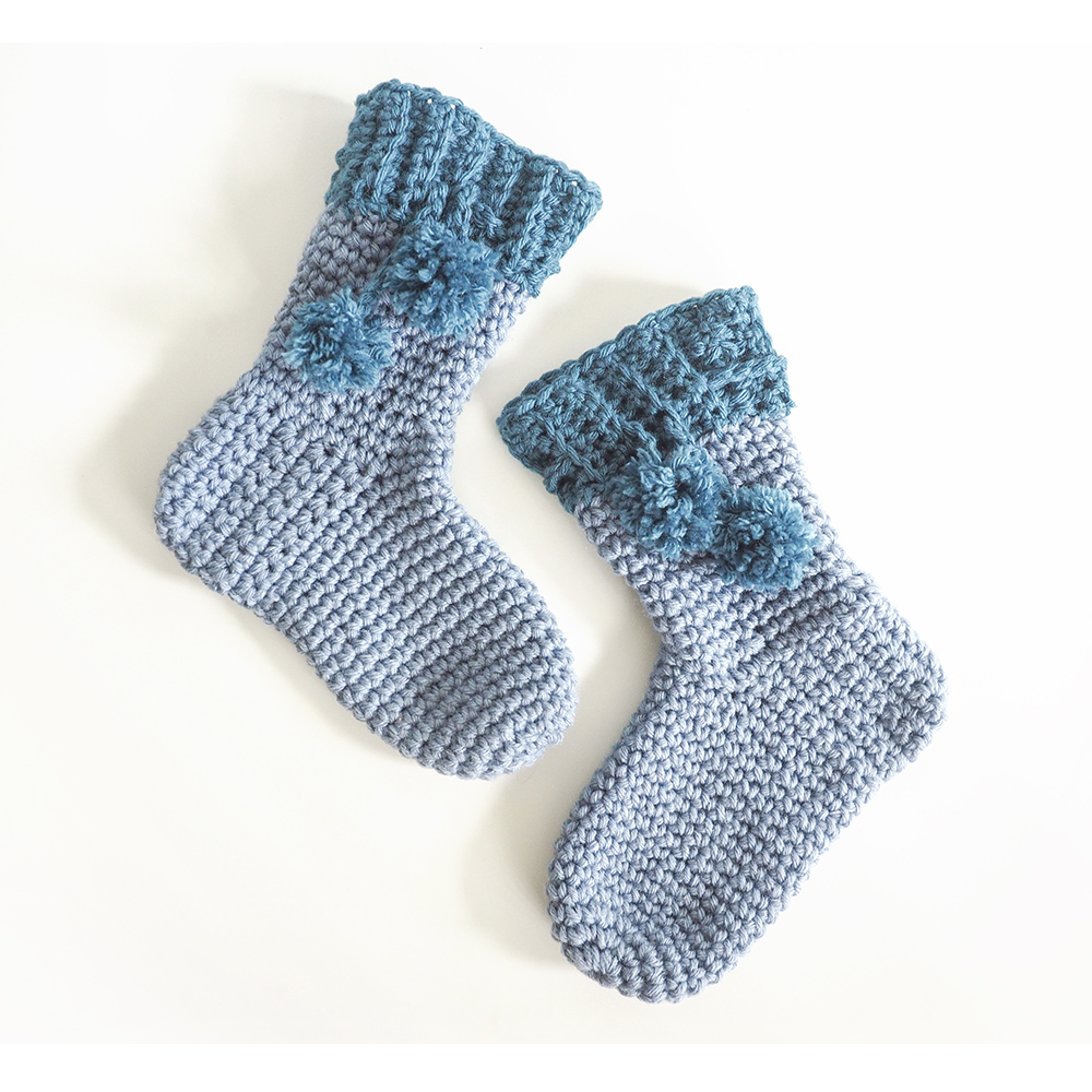 The Pom Pom Slipper Socks make adorable stocking stuffers. #crochetsocks #crochetslippers #crochetpattern #crochetaddict #crochetlove