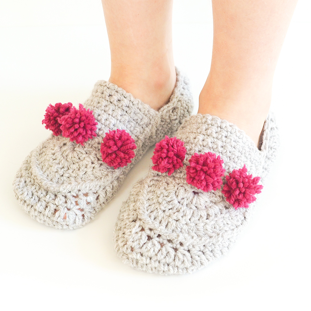 These crochet pom pom slippers are a one size fits all, and are extra comfy. This crochet pattern is easy to make and cozy to wear. #CrochetSlippers #CrochetPattern #CrochetAddict