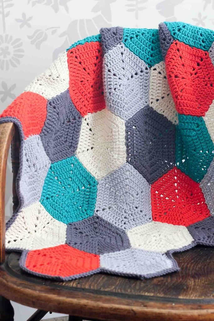 Happy Hexagons - This list has the best crochet afghan patterns out there. From chunky, thick fabrics, to delicate details, you can find whatever you're looking for. #CrochetAfghanPatterns #CrochetPatterns #AfghanPatterns #FreeCrochetPatterns