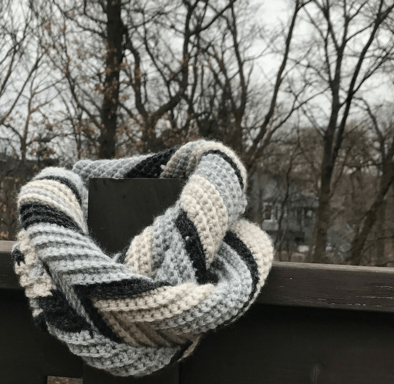Grey Skies Chevron Infinity Scarf - If you're just learning how to crochet, a crochet infinity scarf will be your best friend. Take advantage of this and make one for the people you love. #CrochetInfinityScarf #ScarfCrochetPatterns #CrochetPatterns